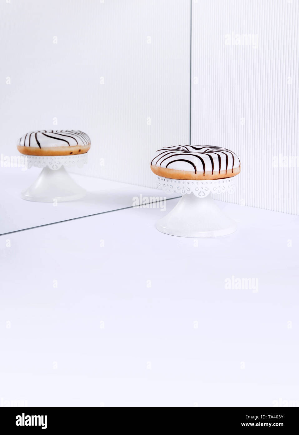 Striped donuts on a white background. Stylish minimal concept - Stock Image