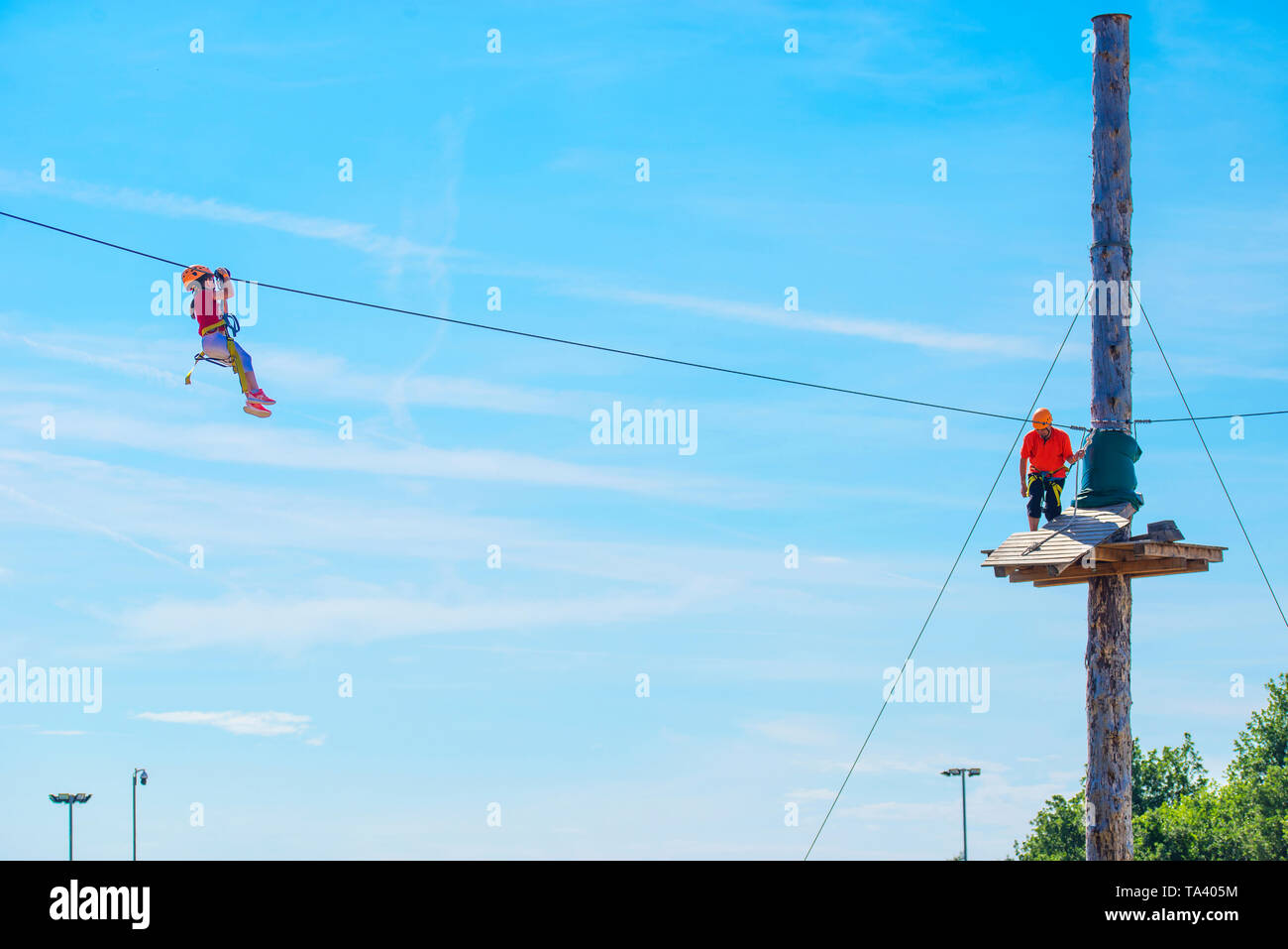 Little brave caucasian 7 years old girlie using a zip line in a rope playground structure in 5 meters high altitude. An indefinited man lend a helping - Stock Image
