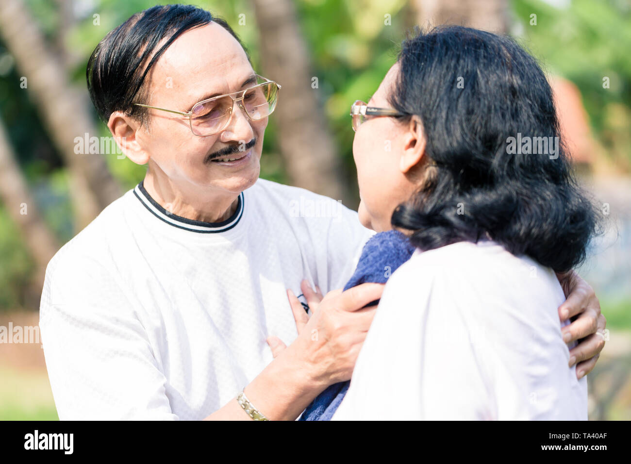 Man wiping sweat of her wife with napkin - Stock Image