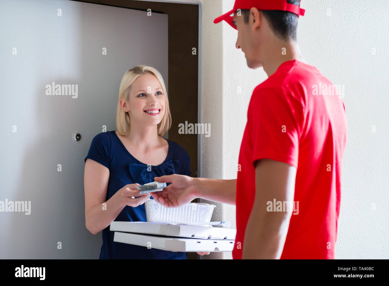 Female customer making payment to delivery man - Stock Image