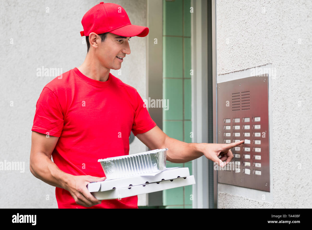 Pizza delivery man carrying boxes using the intercom - Stock Image