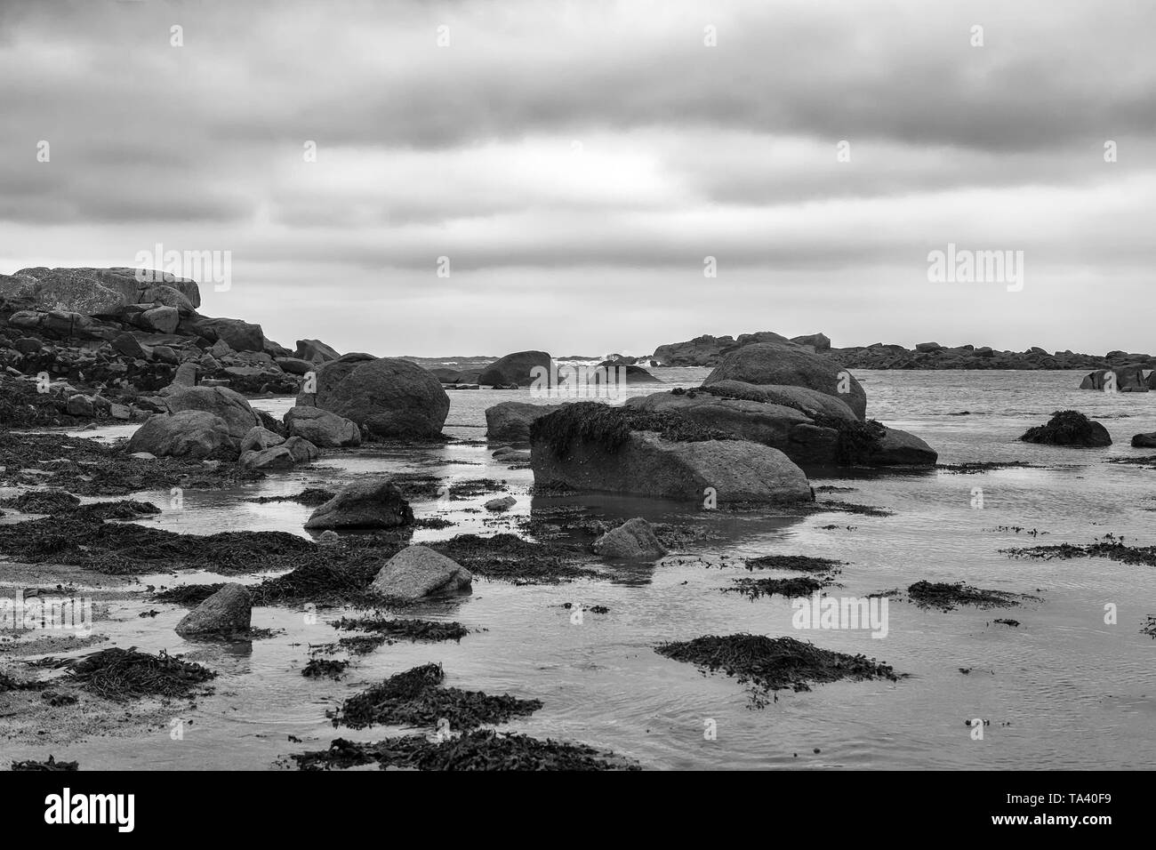 The rocky entrance to Porth Hellick at low tide: St. Mary's, Isles of Scilly, UK: black and white version - Stock Image