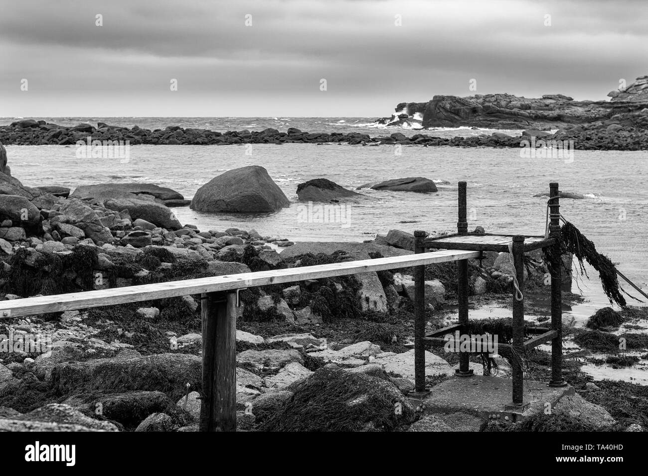 Rickety landing stage in Porth Hellick, St. Mary's, Isles of Scilly, UK: black and white version - Stock Image