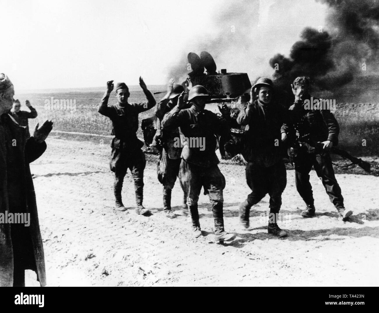A German infantryman (far right) is leading Russian prisoners off. In the background, a burning BT-5 or BT-7. Stock Photo