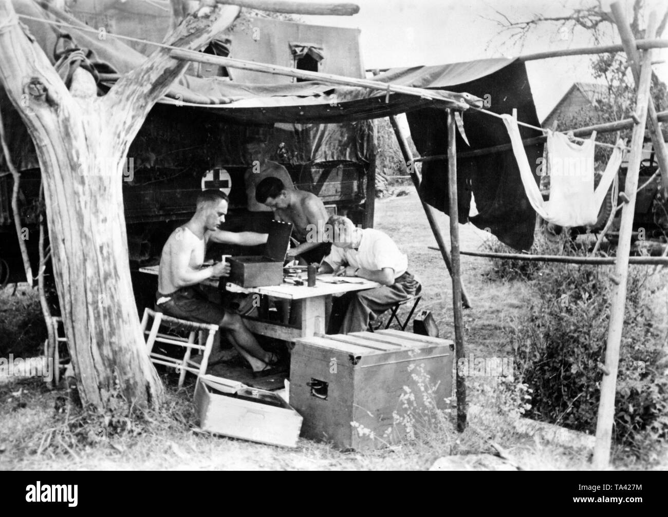 Typing facility of the Wehrmacht. There are no walls, only a provisional roof. Behind it a truck of a medical department. Photo: war correspondent G. Schmidt. Stock Photo