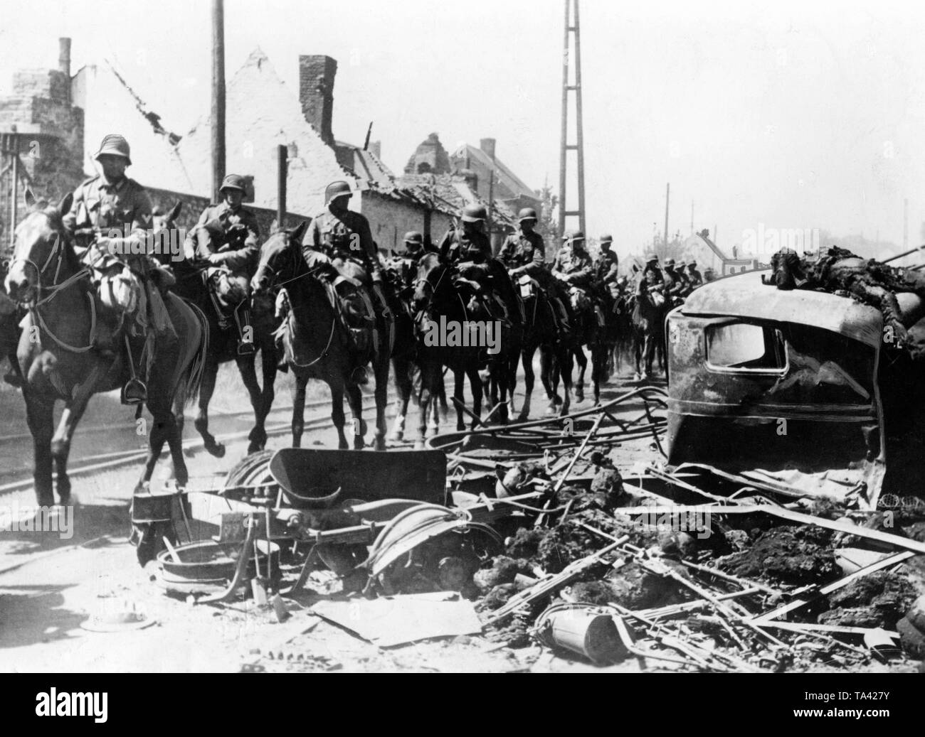 German cavalrymen pass through a French village, right in the picture a destroyed vehicle and the dead crew. Although the Western campaign is more associated with tanks, the Wehrmacht also deployed a complete cavalry division. - Stock Image