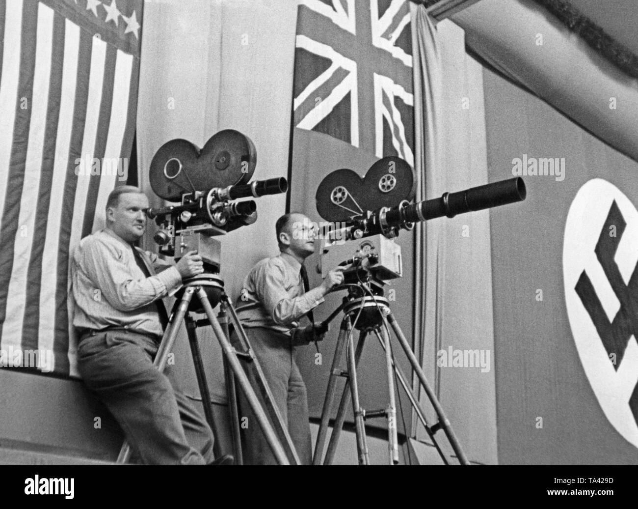 The cameramen Heinz Kluth and Bernhard Juppe shooting 'Der grosse Tag von Hamburg'. In the background, the swastika flag and the flag of Great Britain. - Stock Image