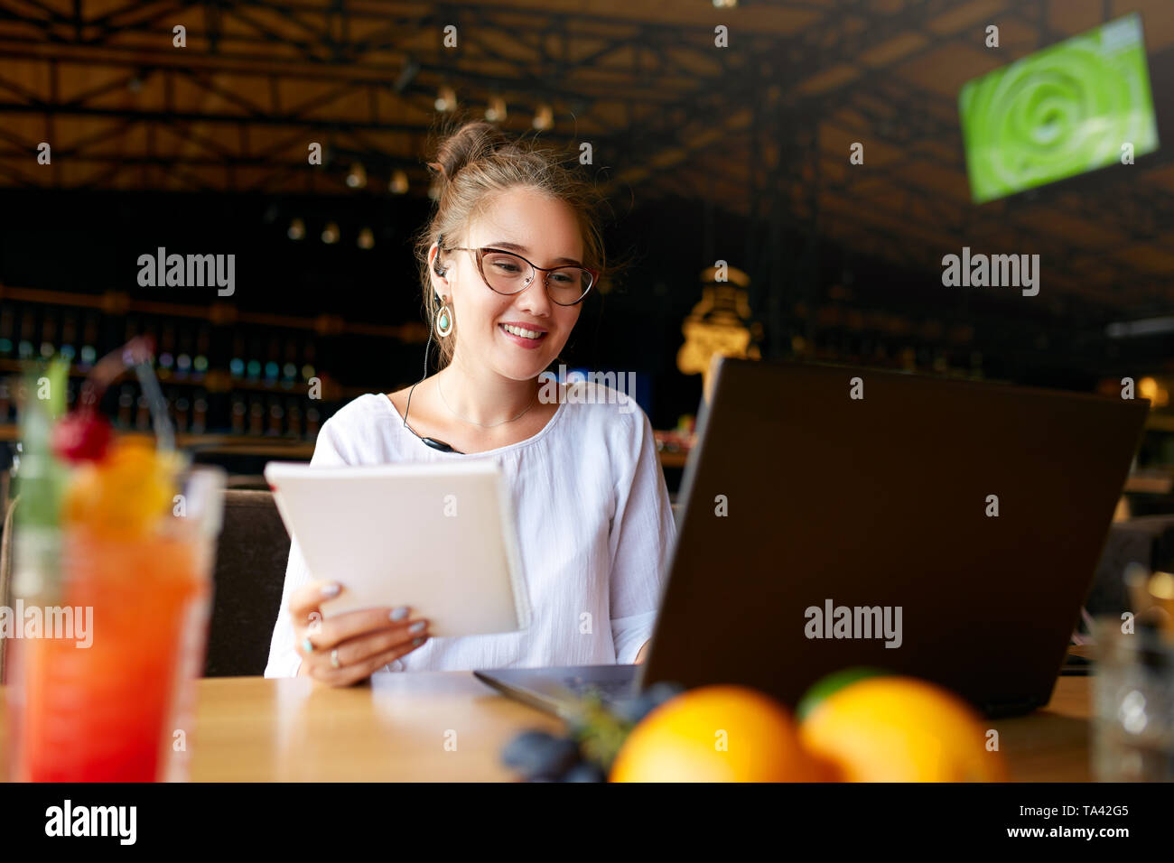 Businesswoman working remotely at cafe with headset and laptop. Mixed race female performing business negotiations on conference video chat. Telecommu Stock Photo