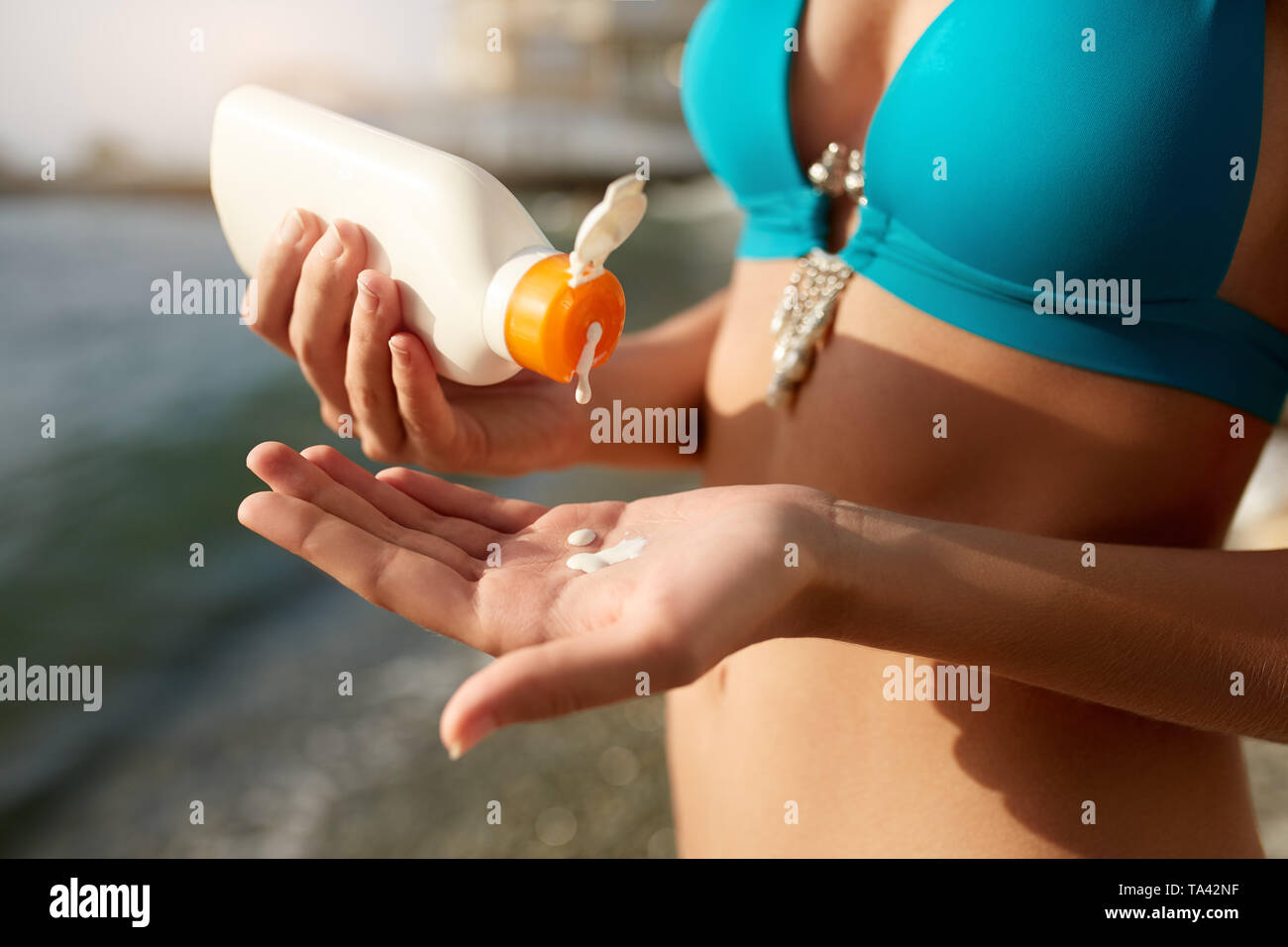 Woman hands putting sunscreen from a suntan cream bottle. Caucasian female squeeze suncream on her hand. Tanned girl wearing blue bikini swimsuit on t - Stock Image