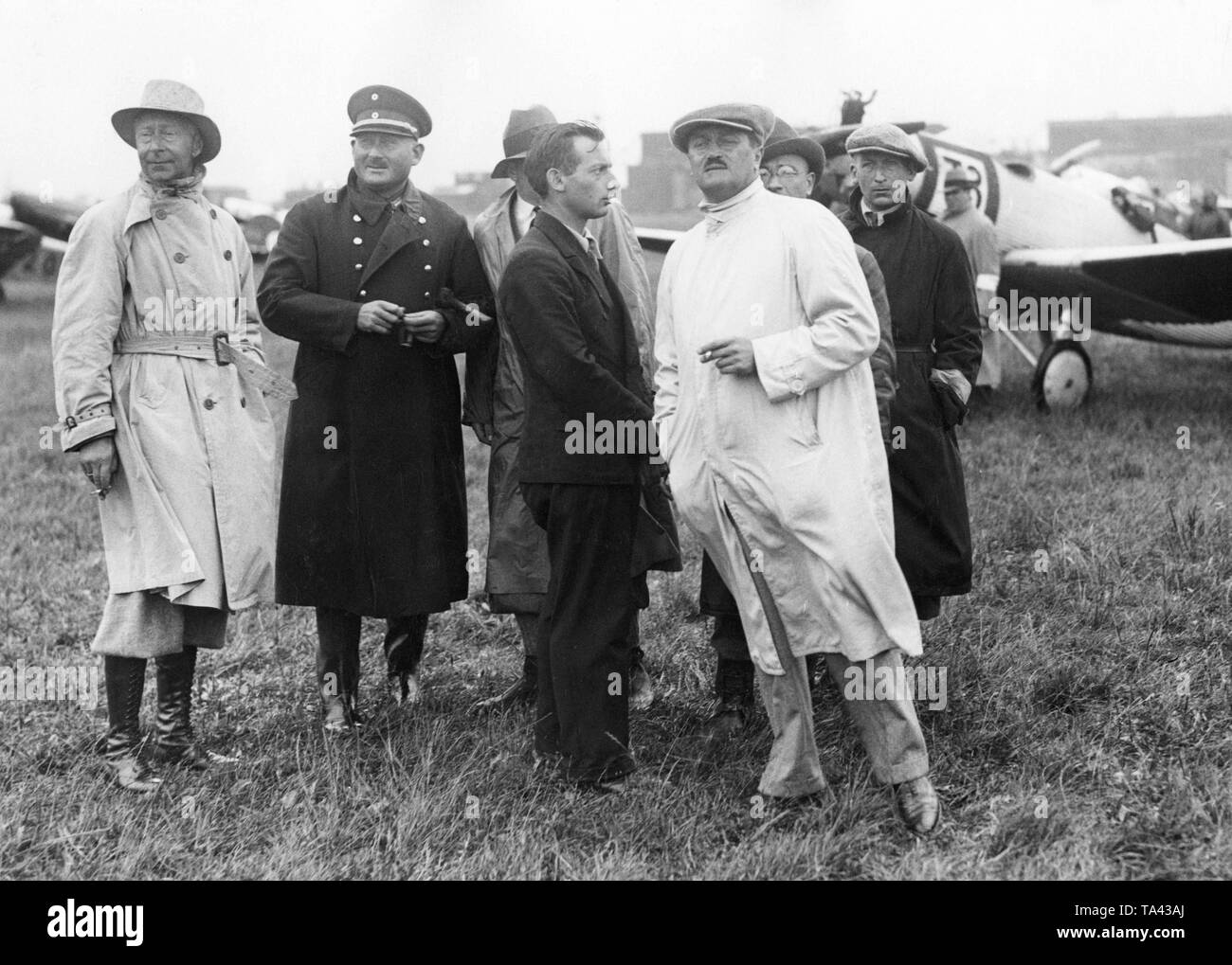 Crown Prince Wilhelm (left) and the aircraft designer Helmut Hirth (4th from left in a light coat) watch the start of the Deutschlandflug with their companions on the airfield Berlin-Staaken. - Stock Image