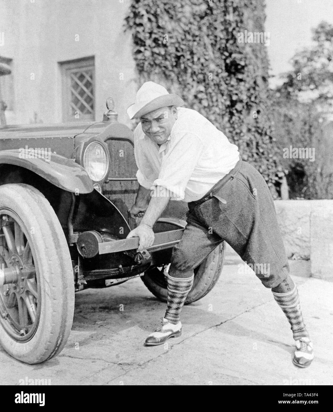 The tenor Enrico Caruso demonstrates the operation of the starter crank on a car. Stock Photo