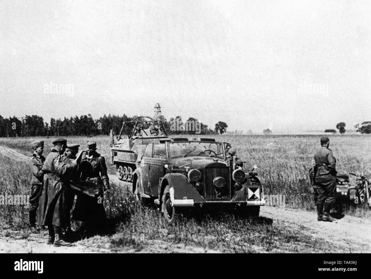 General Heinz Guderian (3rd from left, front), commander of the 2nd Panzer Group of Army Group Center on the day of the attack at the Bug. In the background, a Soviet observation tower. The vehicle on the left is an armored personnel carrier of the type Sd.Kfz. 250 with radio equipment. Stock Photo
