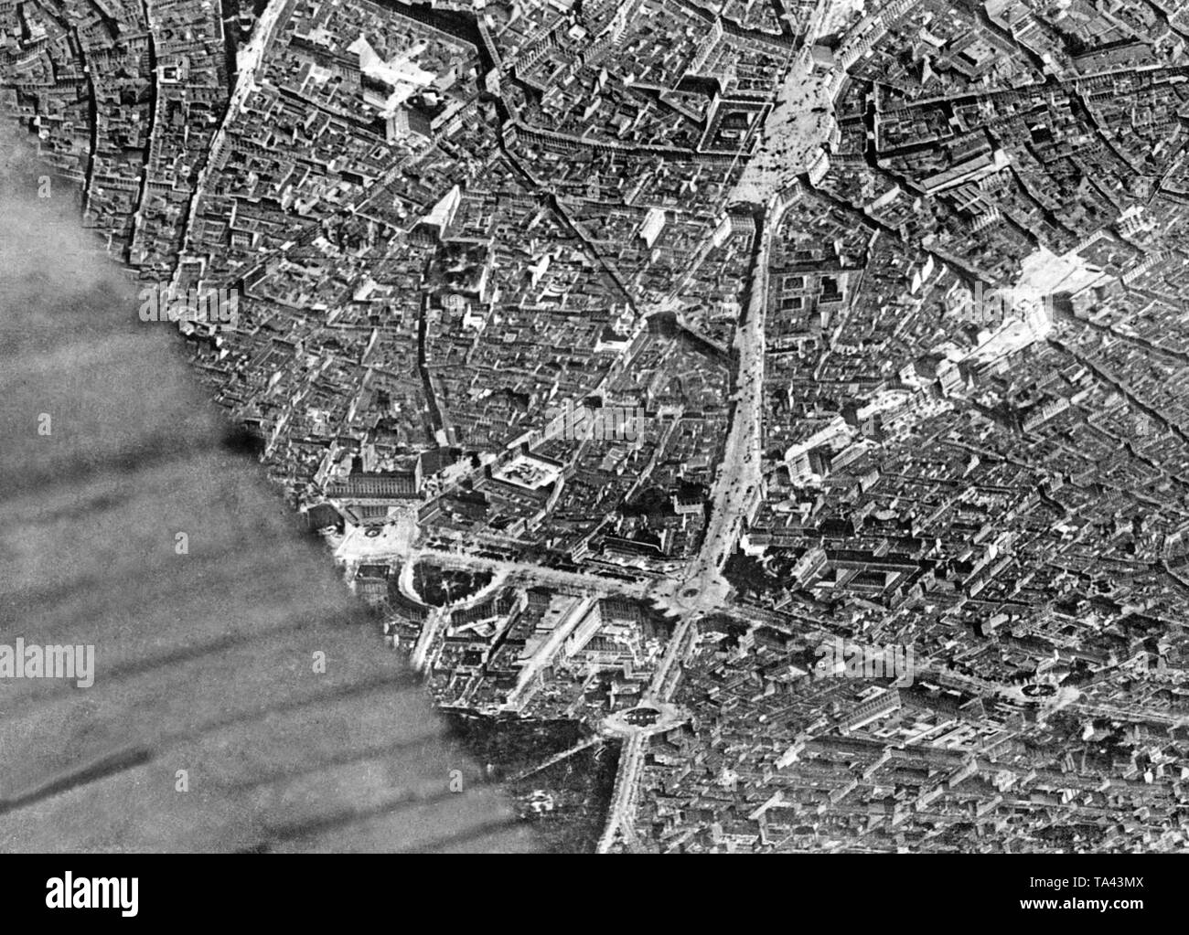 Aerial photo of the center of Madrid during the Spanish Civil War on November 9, 1936. Below in the center, the Puerta del Sol, right next to it, the Gran Via, which was still under construction. Above in the center, the Plaza de Cibeles with the Town Hall of Madrid (white, towers) and the Puerta de Alcala with the gate at the entrance to the Retiropark. To the left, the Plaza del Colon, on the right, the Plaza de la Lealtad with the Madrid Stock Exchange. Covered by the wing: the Prado. - Stock Image