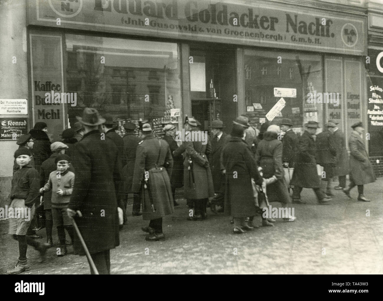 Looting at the grocery store Eduard Goldacker Nachf. (owners Gusowski and van Groenenbergh) GmbH during the Great Depression. Outside the store are policemen and onlookers. The Jewish owner had to close the business in 1933. - Stock Image