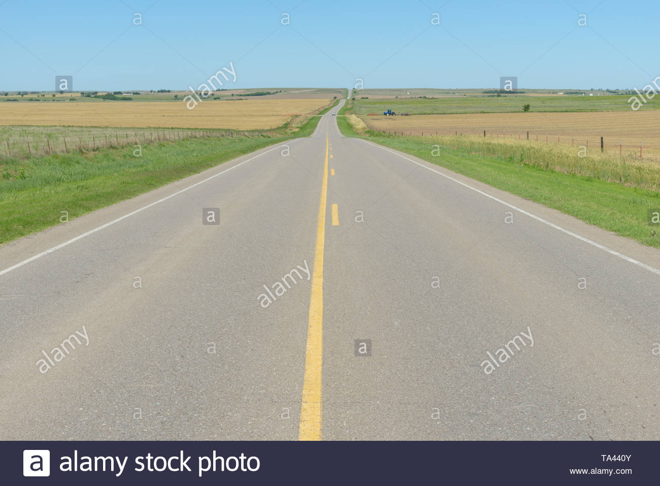 A straight highway runs through wheat fields and agriculture of the Great Plains state of Oklahoma. Stock Photo