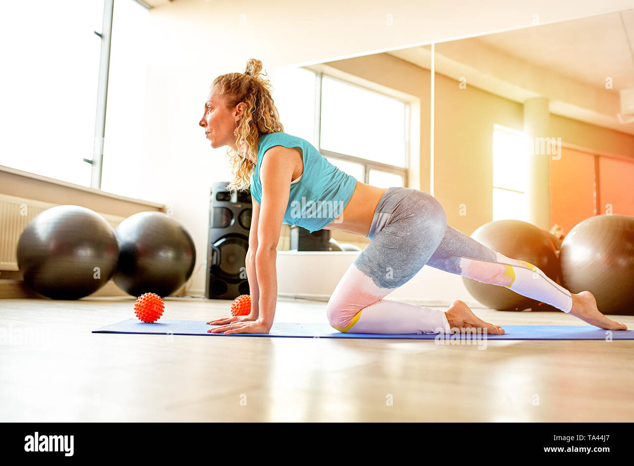 Great progress. Young beautiful woman in sportswear doing stretching in front of window at gym Stock Photo