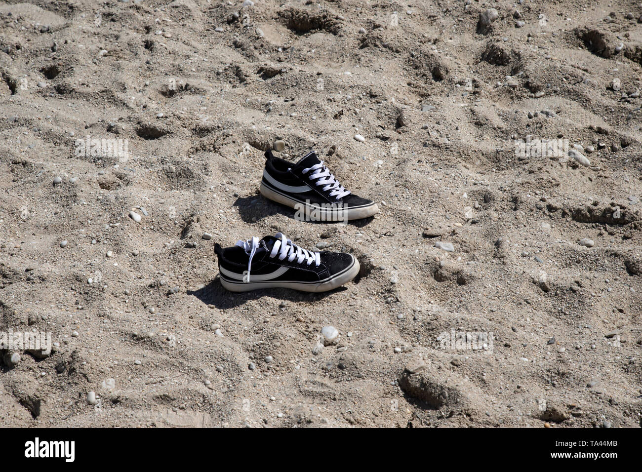 Young child's trainer shoes abandoned on a sandy beach in Swanpool, West Cornwall U.K. - Stock Image