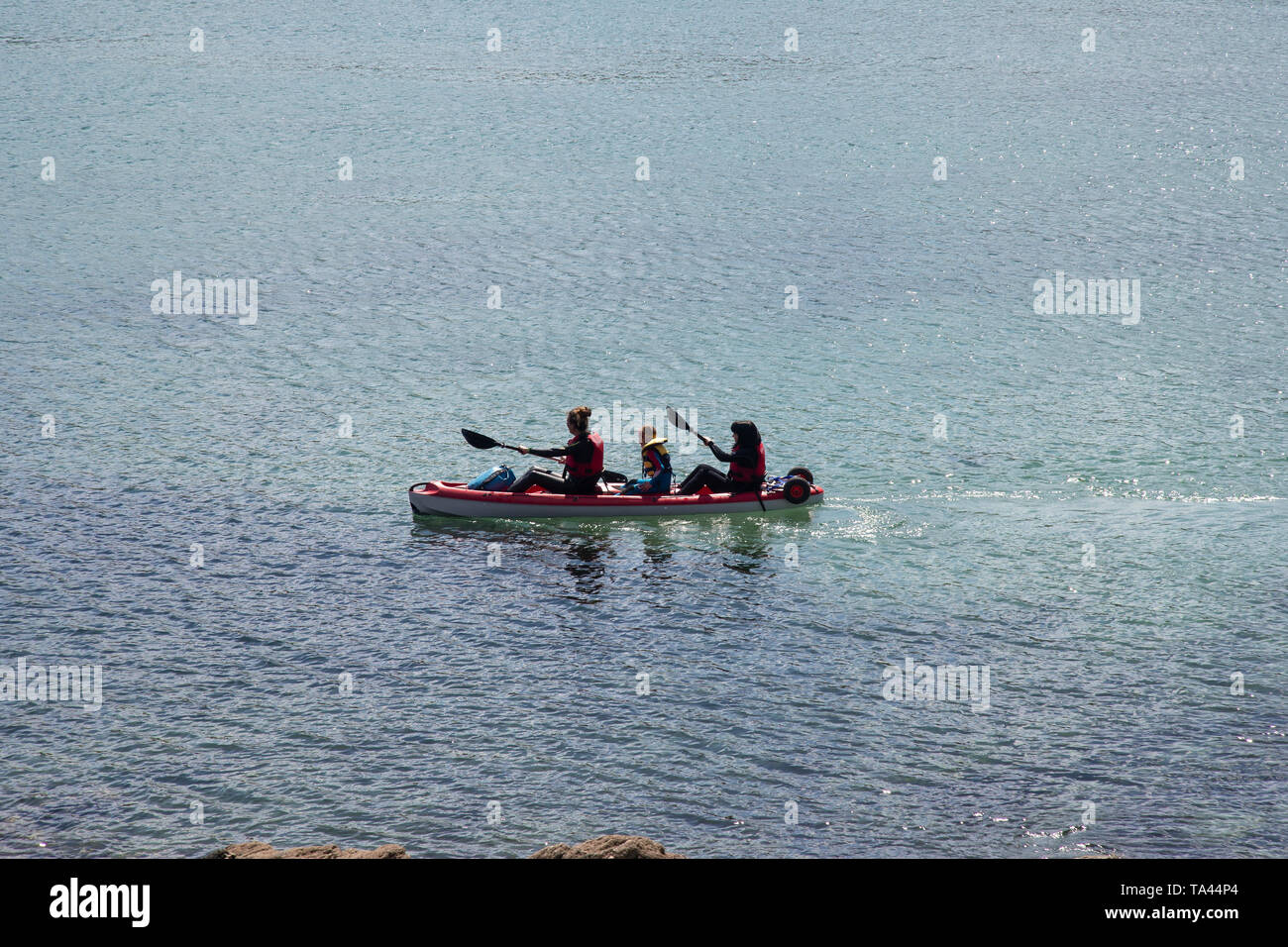 Two adults and a child kyaking in Swanpool cove near Falmouth in Cornwall, U.K. - Stock Image