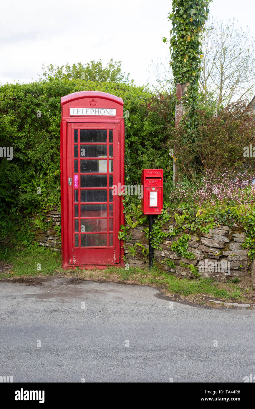 A traditional British red telephone box and Lamp box style postbox in a rural setting in Cornwall - Stock Image