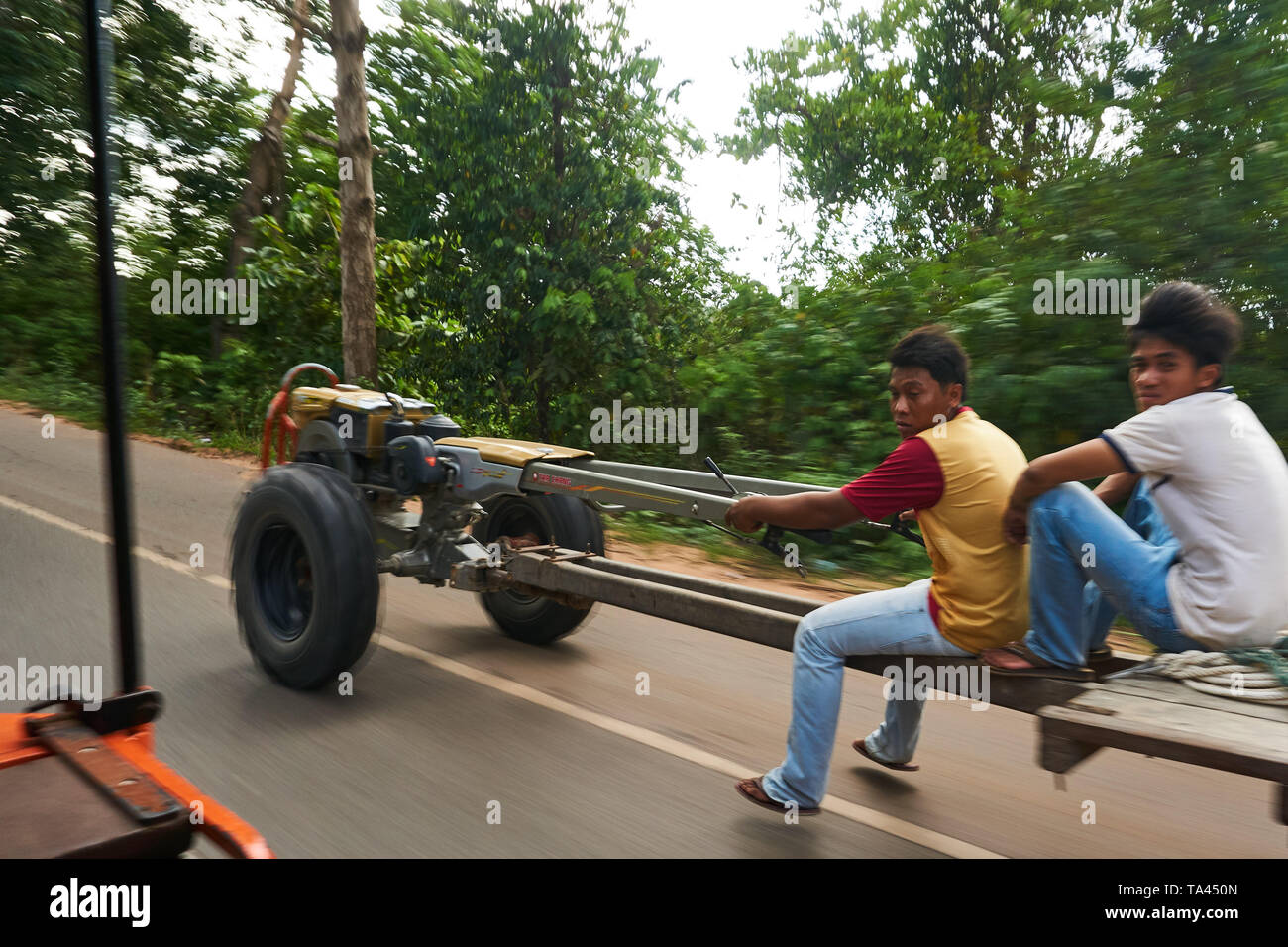 Two Cambodian young men or teenagers drive a creative, homemade vehicle or tractor trailer using an engine and farm equipment parts. - Stock Image