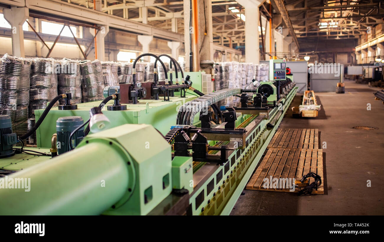 Production machine for metal pipe. powerful new conveyor in modern plant - Stock Image