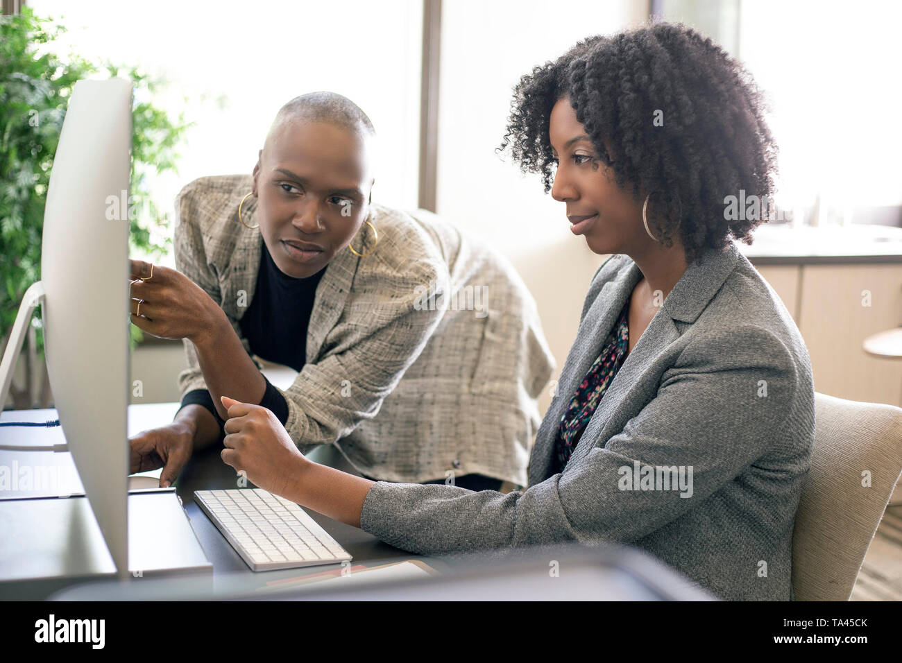 Black African American female co-workers having a business problem and annoyed or upset at each other.  The women lack teamwork or made a mistake at w - Stock Image