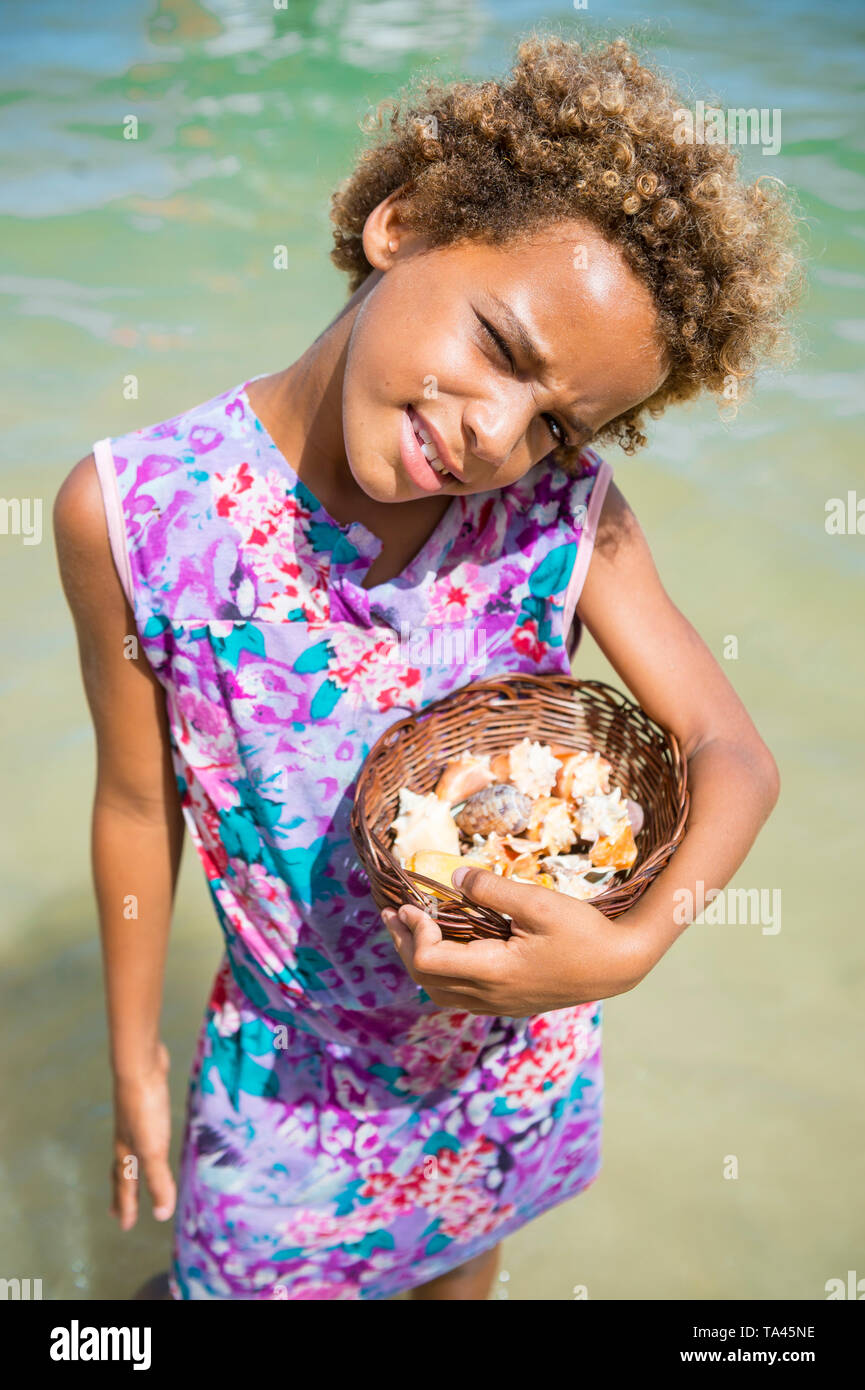 CAIRU, BRAZIL - FEBRUARY 2018: A young Brazilian girl sells souvenir shells from a small woven basket to visitors arriving on boat tours. Stock Photo