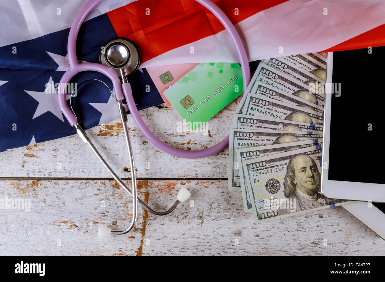Stethoscope and tablet on credit card us dollar bill american health care service - Stock Image