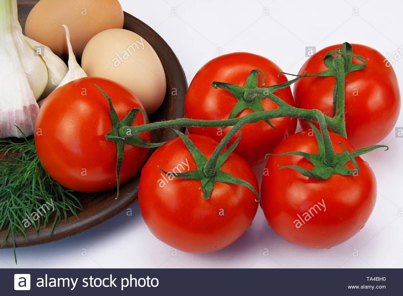 Five red ripe tomatoes on a twig and two eggs with a head of garlic on a clay plate on a white background close-up - Stock Image