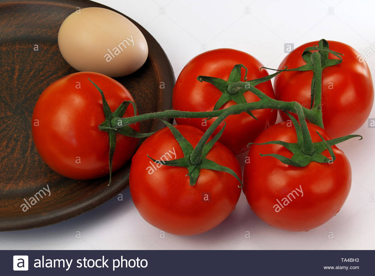 Five red ripe tomatoes on a twig and an egg on a clay plate on a white background close-up - Stock Image