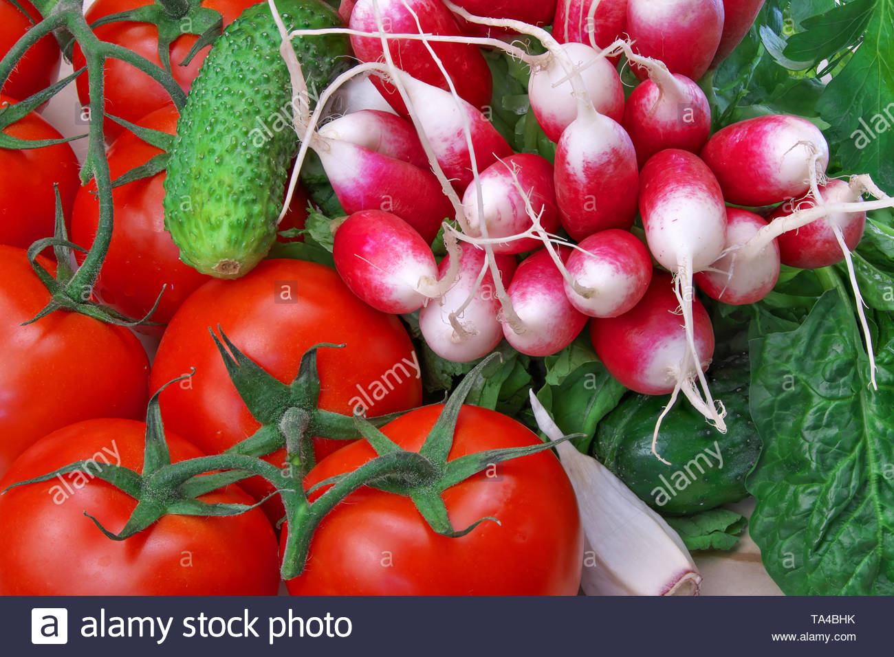 Still-life with red ripe tomatoes and other vegetables with greens close-up - Stock Image