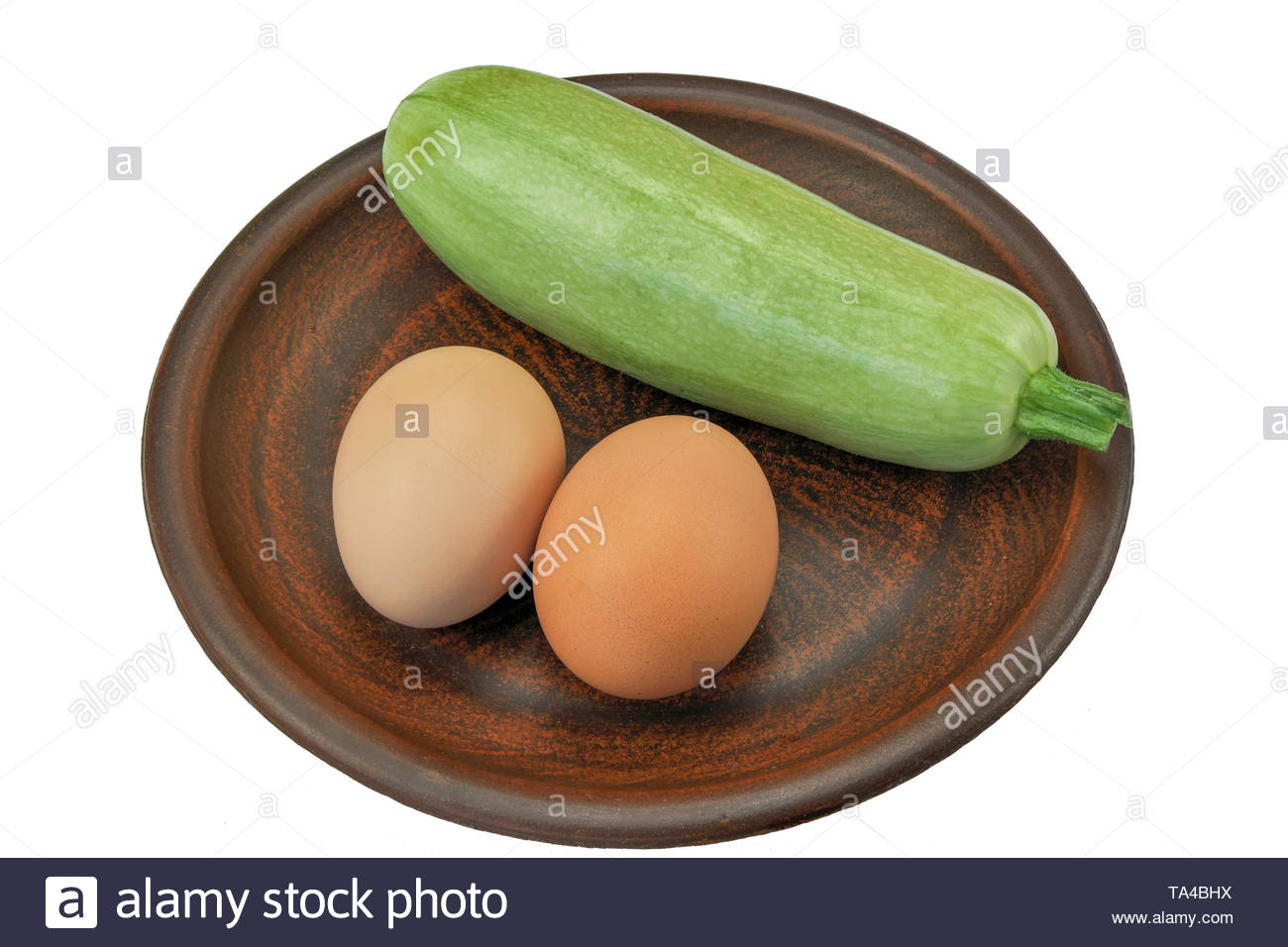 Fresh green zucchini and two eggs on a brown clay plate close-up isolated on a white background - Stock Image