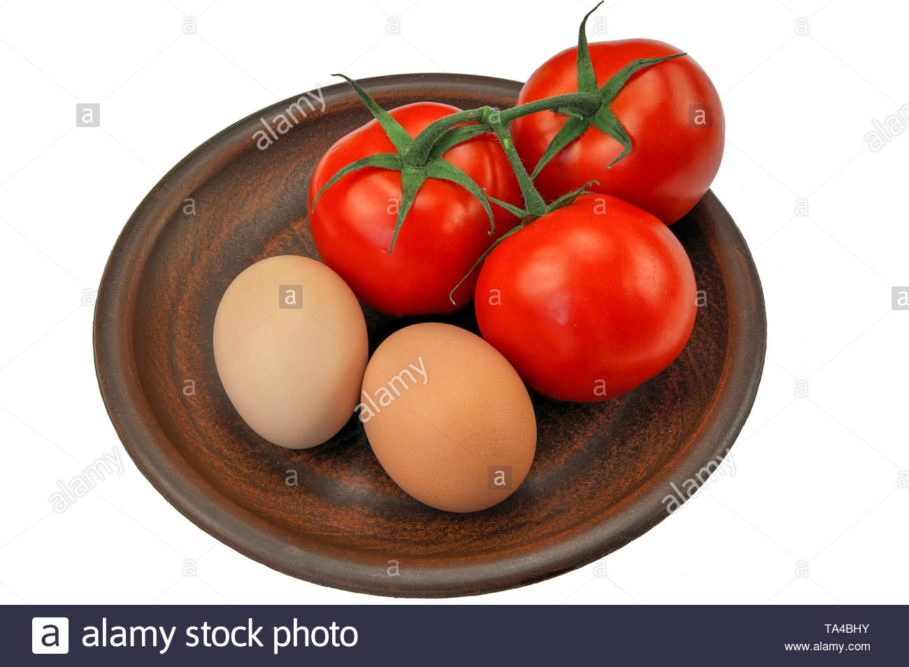 Three red ripe tomatoes on a twig and two eggs on a brown clay plate on a white background close-up - Stock Image