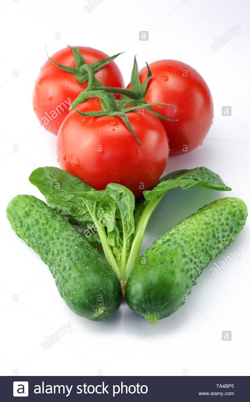 Three red ripe tomatoes on a twig and two cucumbers with a bunch of spinach on a white background close-up - Stock Image