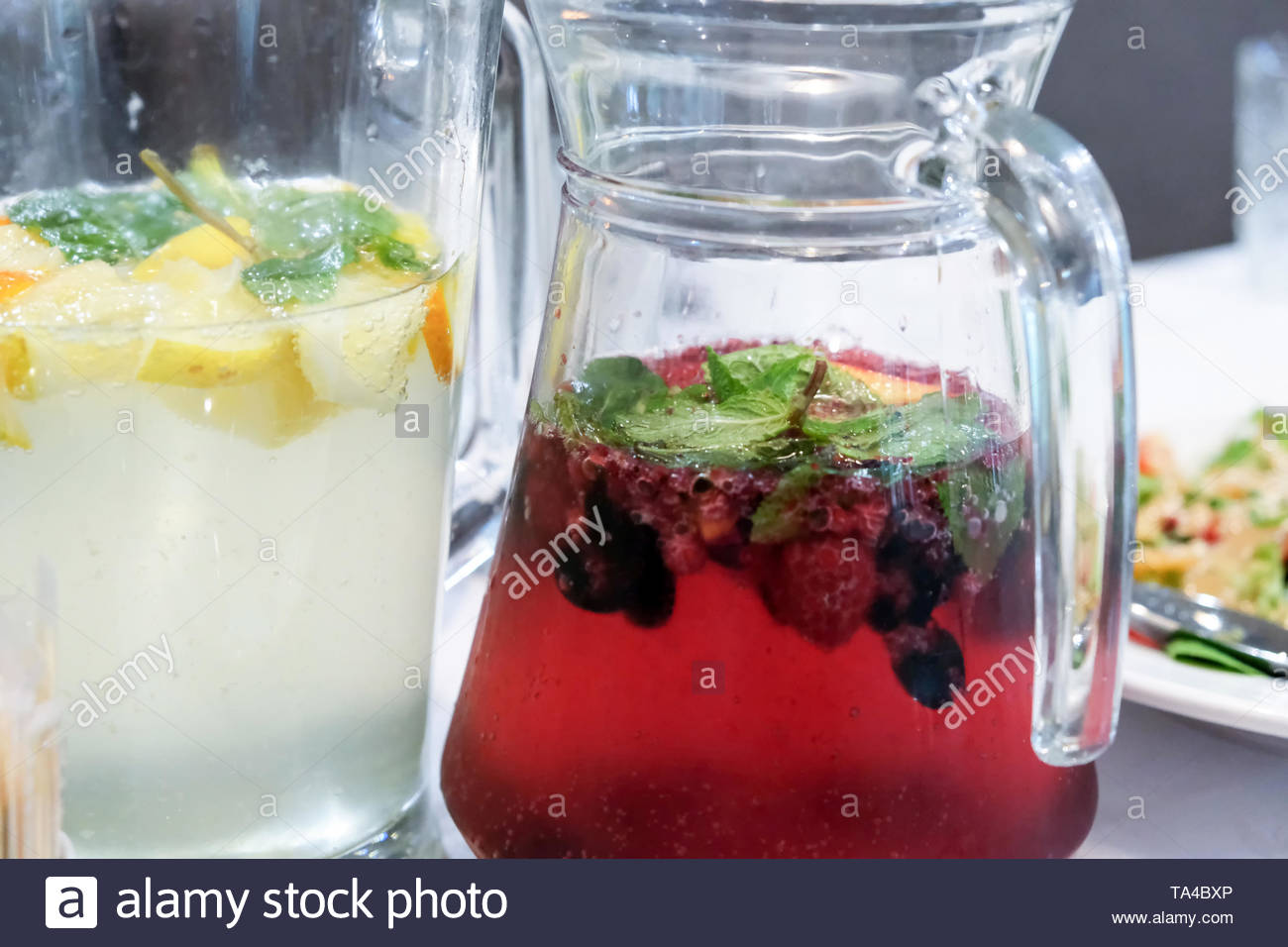 Glass jars with homemade citrus and berry drinks close up Stock Photo