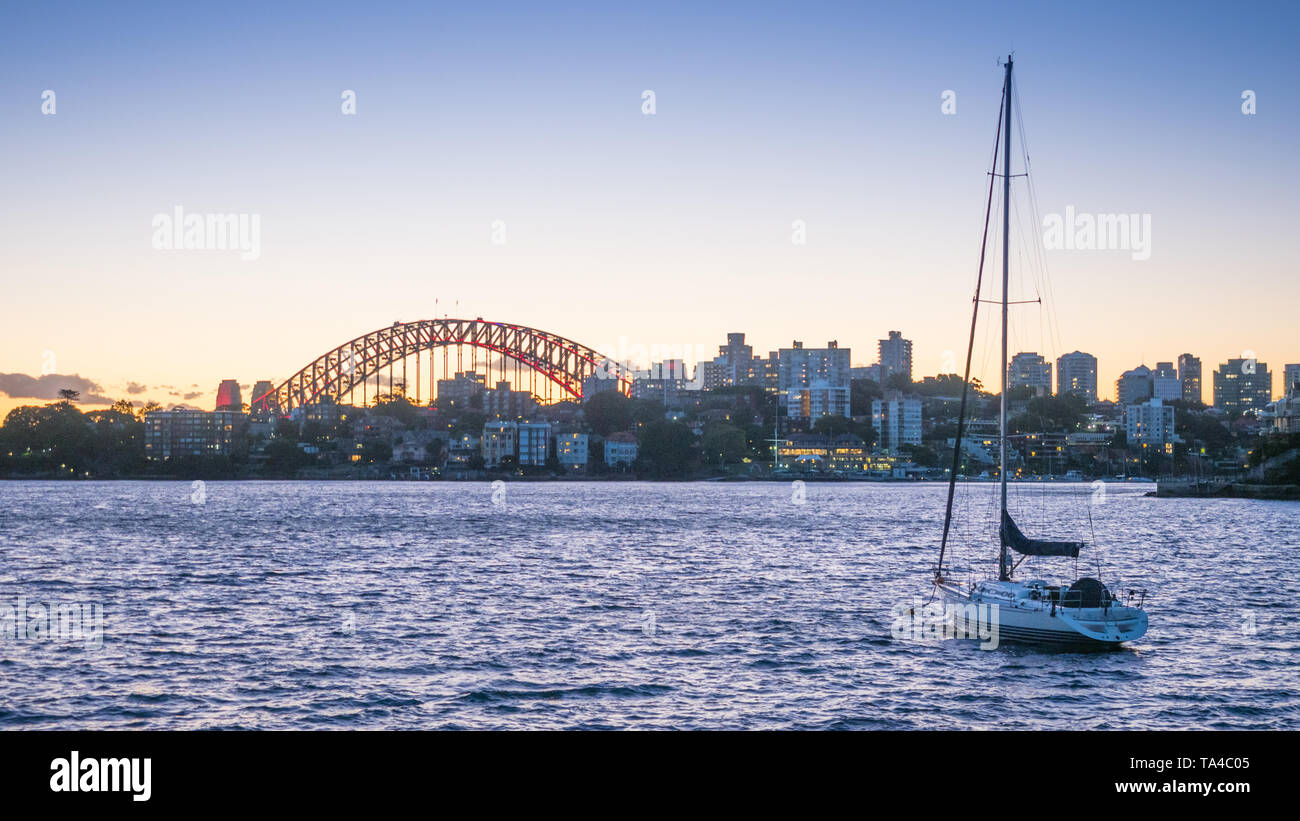 A yacht moored in Sydney Harbour at sunset, with the Sydney Harbour Bridge in the background. Stock Photo