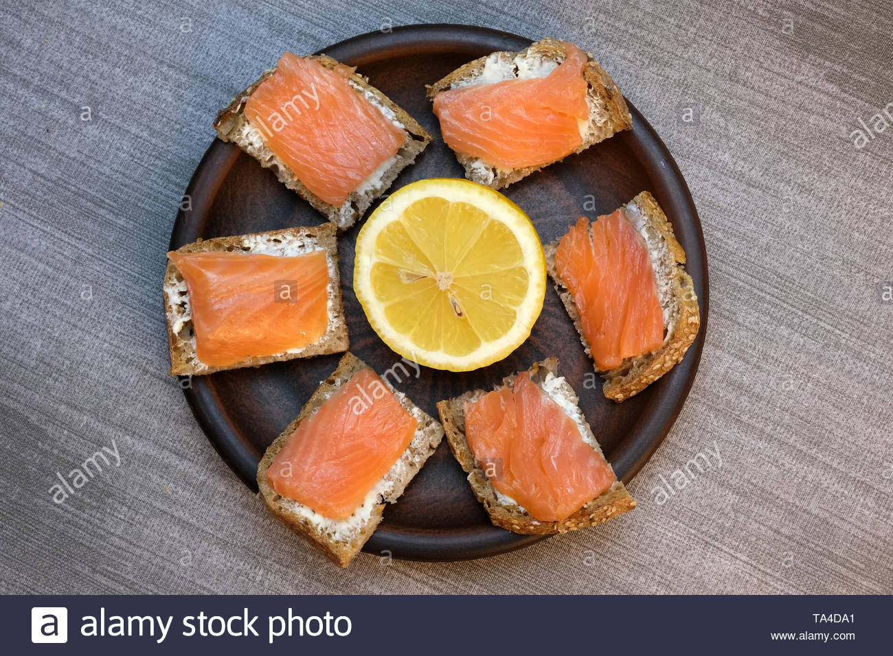 Small sandwiches on homemade bread with butter and red fish on a brown clay plate on a table with a gray tablecloth - Stock Image