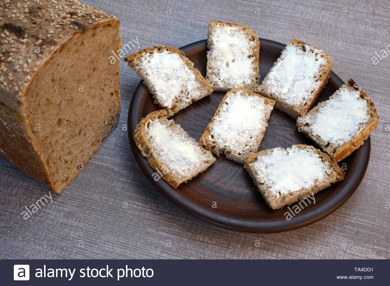 Small sandwiches on homemade bread with butter on a brown clay plate on a table with a gray tablecloth - Stock Image