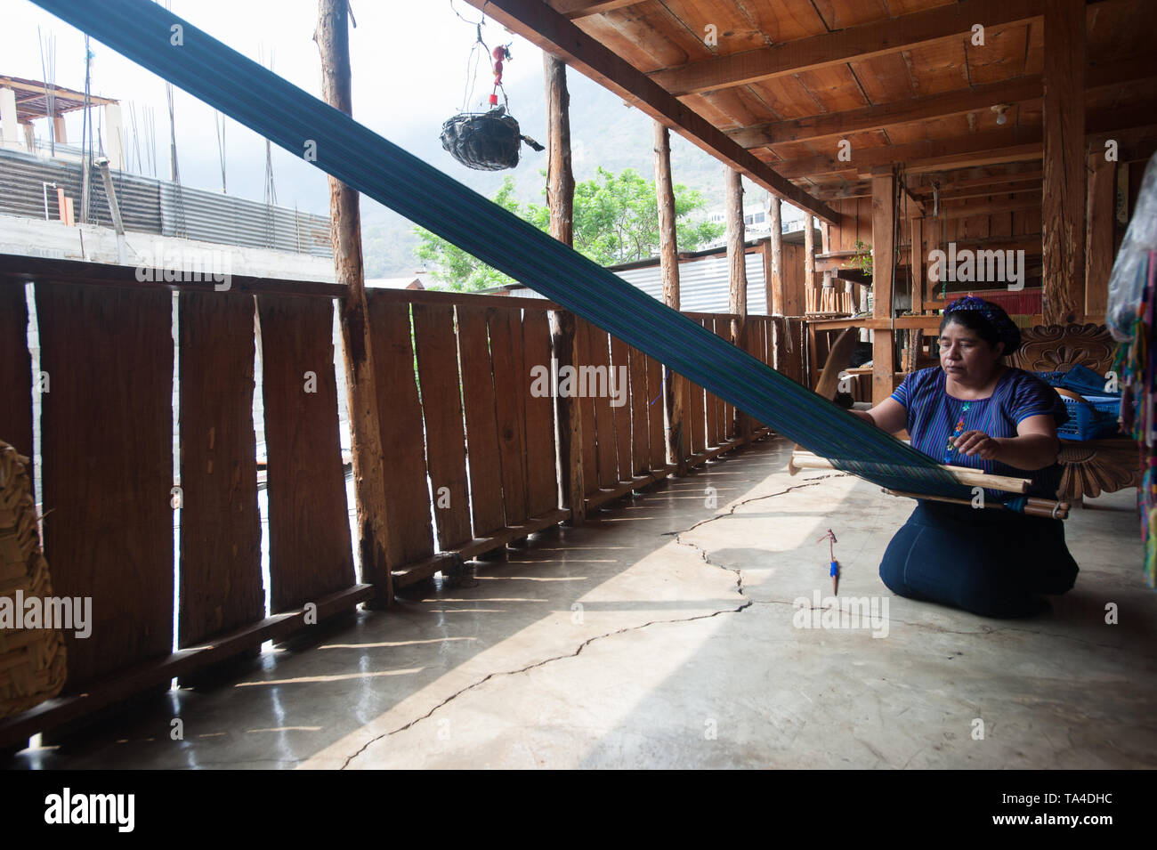 A maya indigenous woman weaves on backstrap loom in San Antonio Palopo, Solola, Guatemala. - Stock Image