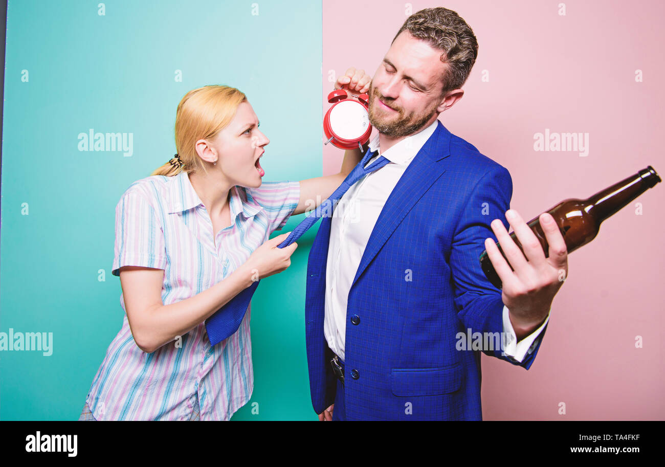 It is too late. Angry wife meeting drunk husband late at home. Man suffering from alcoholism. Businessman with alcohol bottle and woman with alarm clock. Addictive alcoholism or alcohol abuse. - Stock Image