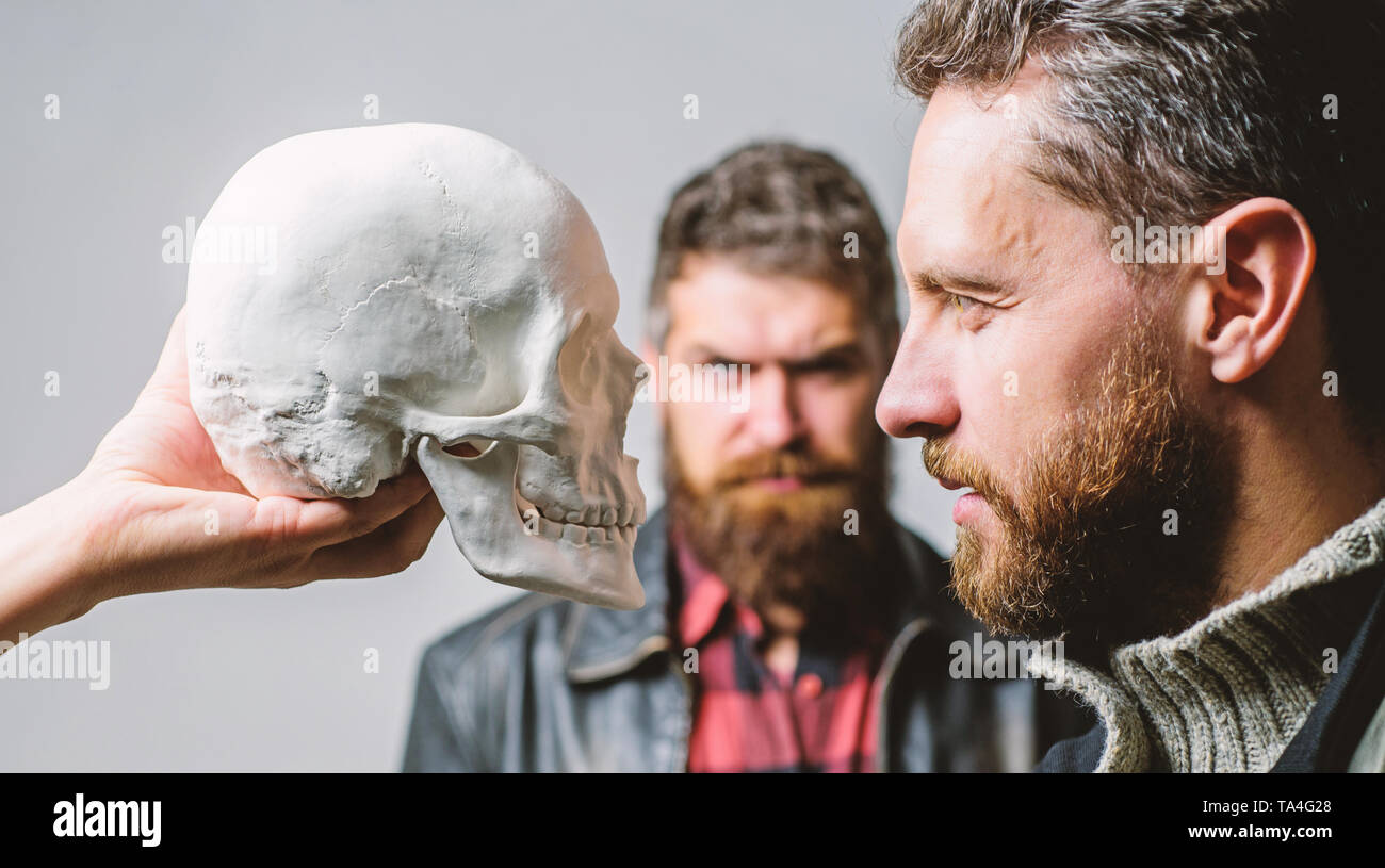 Be brave. Focused on breaking fear. Psychology concept. Human fears and courage. Looking deep into eyes of your fear. Man brutal bearded hipster looking at skull symbol of death. Overcome your fears. - Stock Image