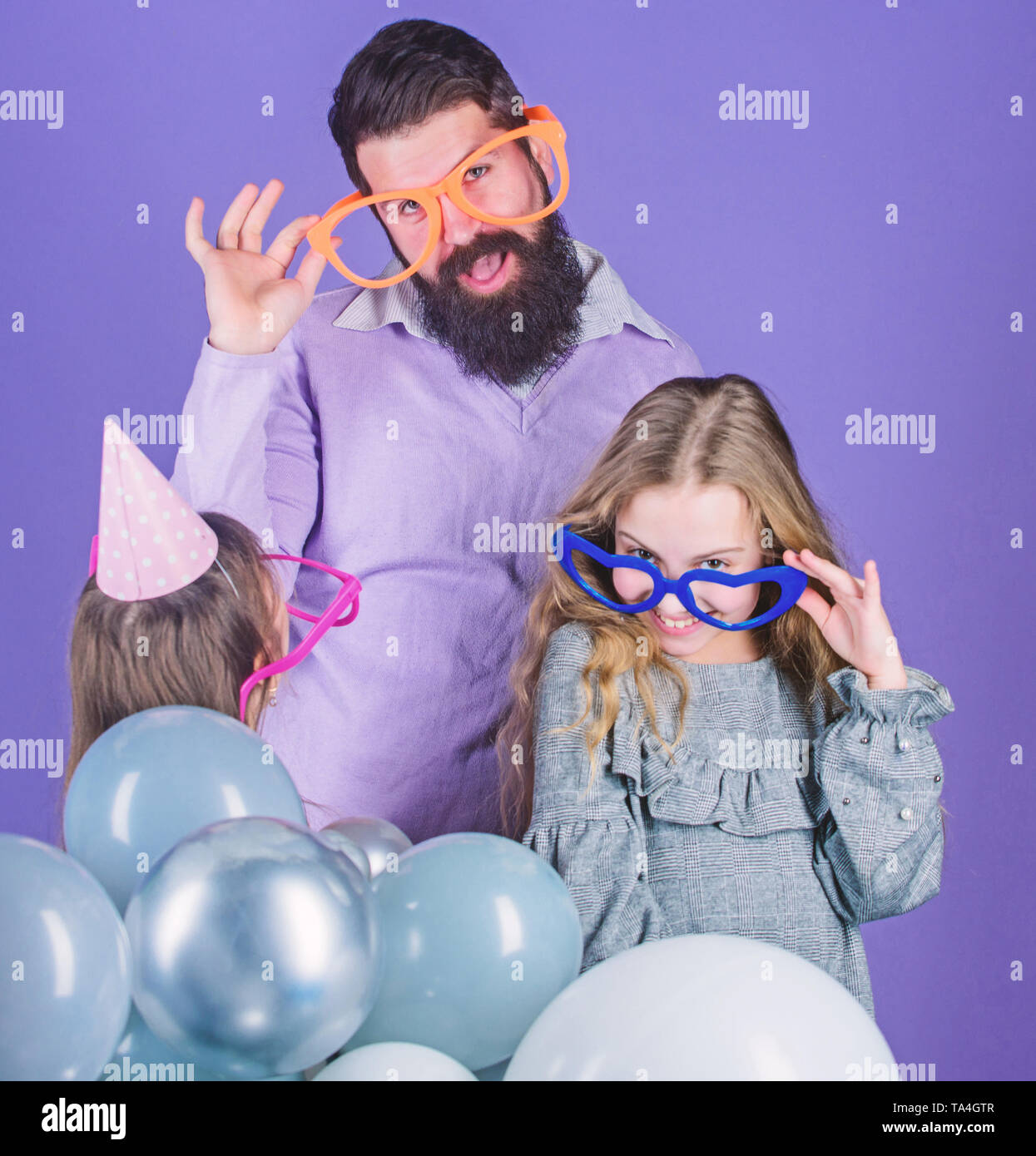 Friendly family wear funny party accessories. Fathers day. Daughters need father actively interested in life. Single father. Birthday party. Father with two daughters having fun. Fatherhood concept. - Stock Image