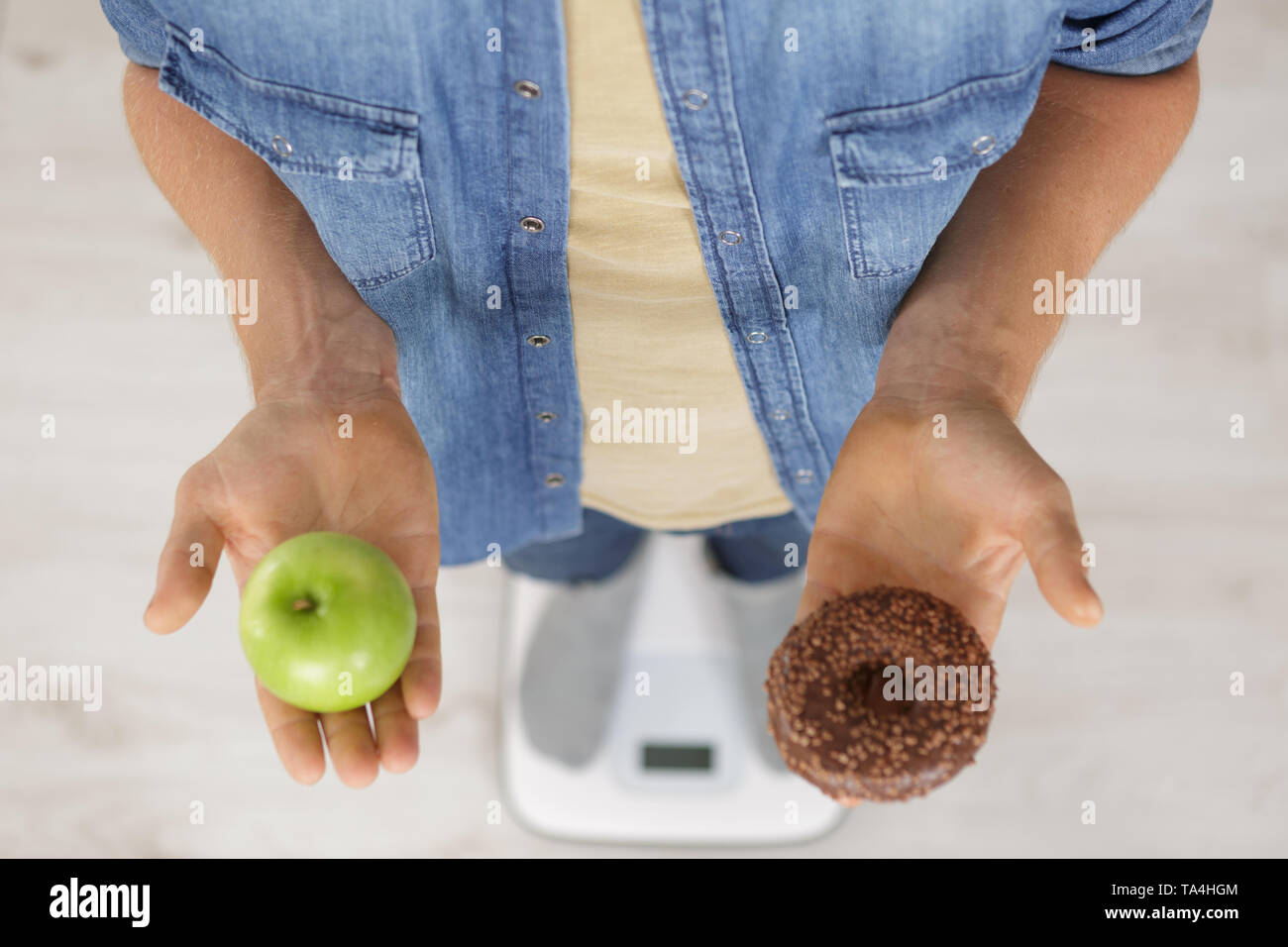 choosing between donut and apple - Stock Image