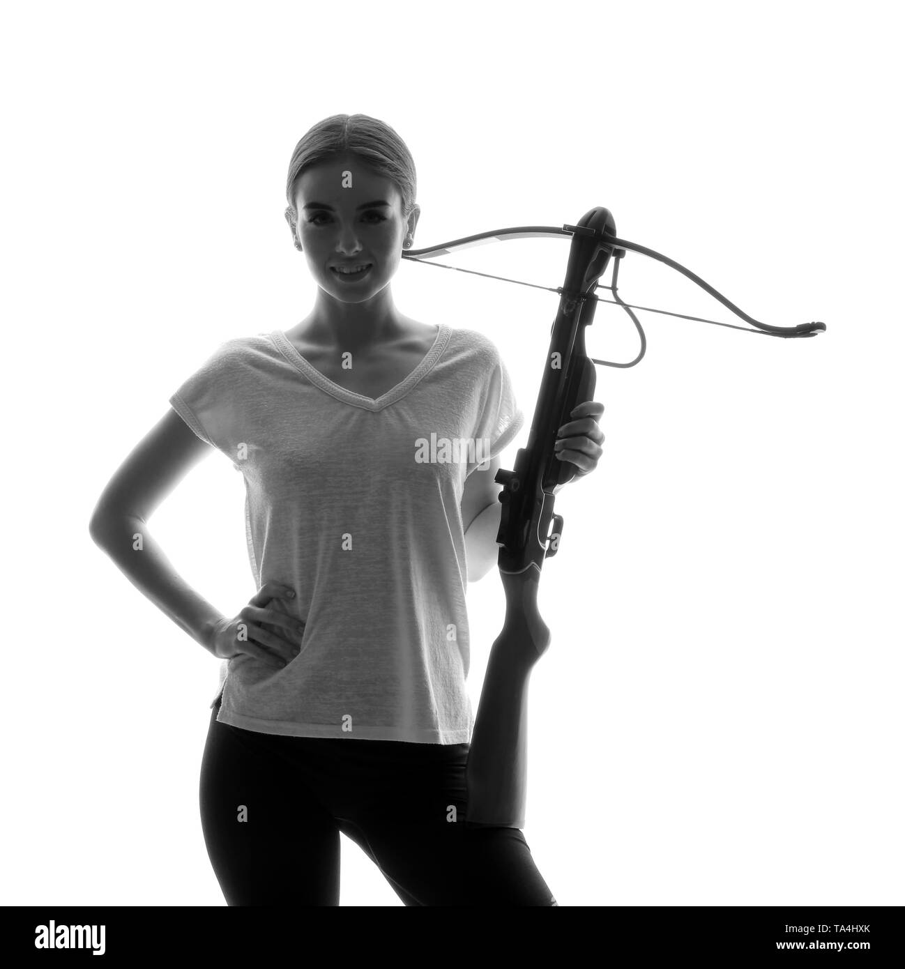 Portrait of beautiful woman with crossbow on white background - Stock Image