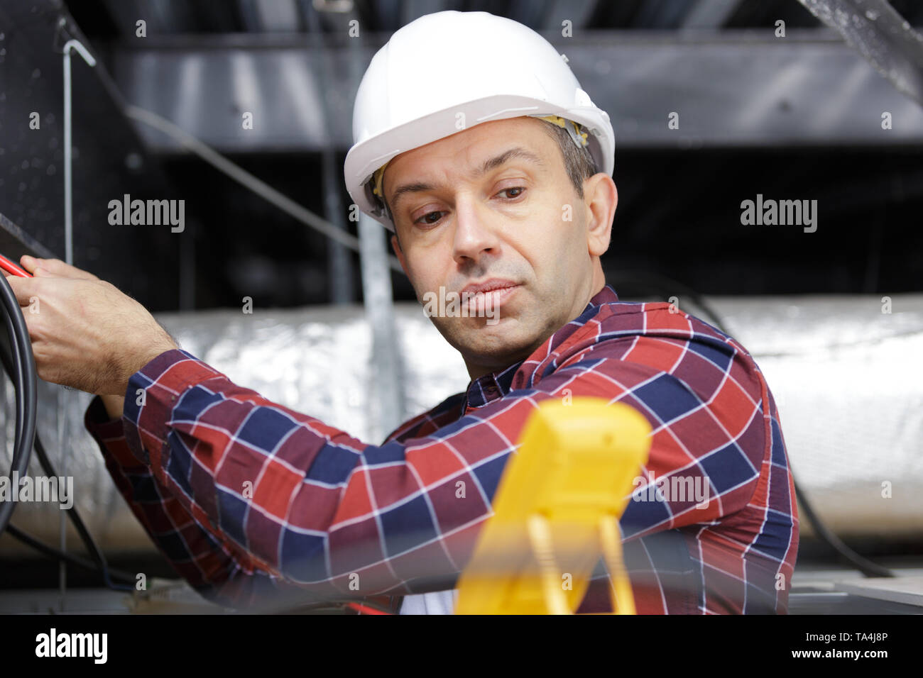 electrician measuring voltage of cables - Stock Image