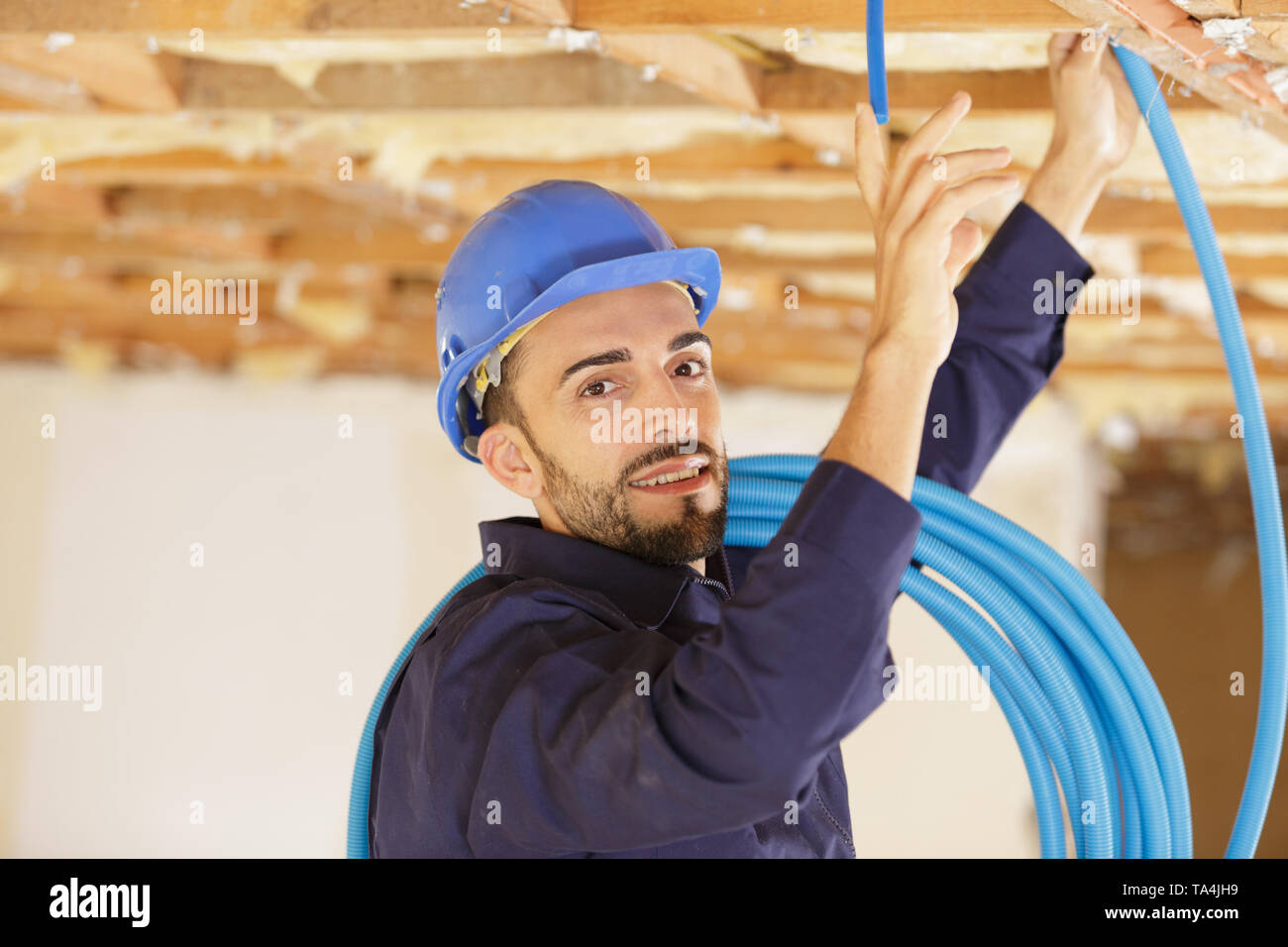 worker sets the ceiling profile in new flat - Stock Image