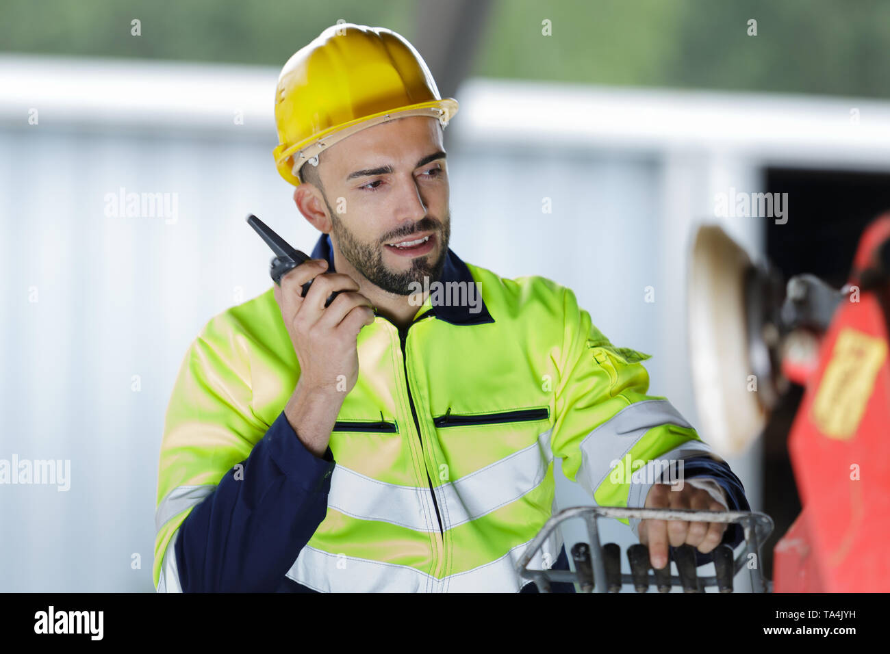 male engineer communicating on walkie-talkie at site - Stock Image