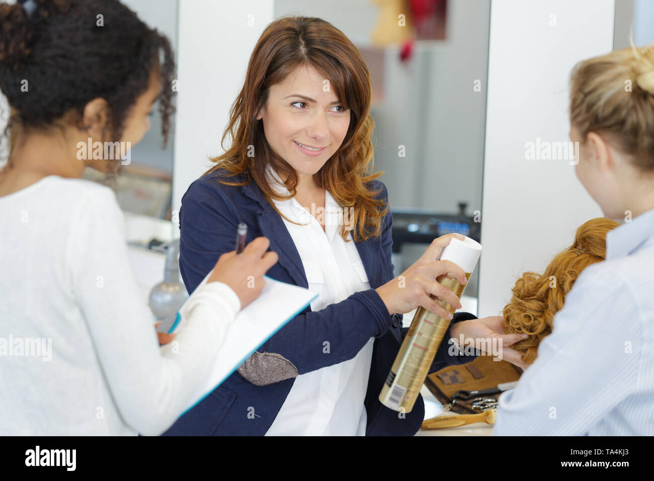 hairdresser demonstrating use of hair spray to trainees - Stock Image