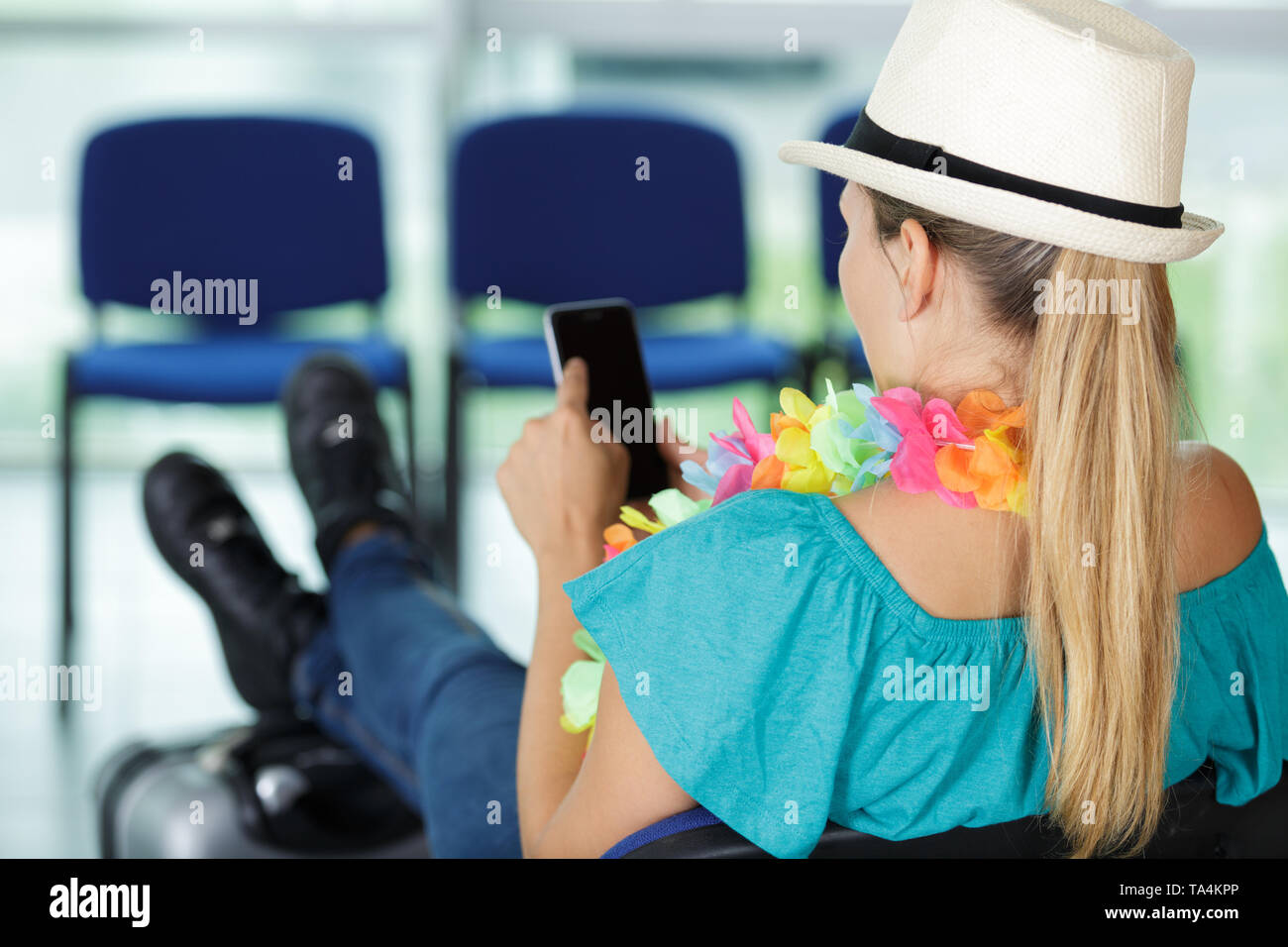 woman using her phone in airport - Stock Image