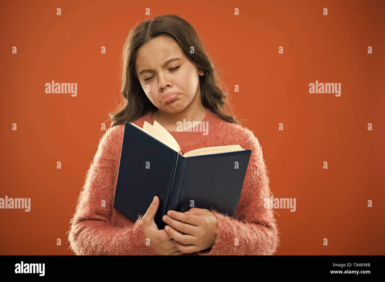 Girl hold book read story over orange background. Child enjoy reading book. Book store concept. Wonderful free childrens books available to read. Childrens literature. Sad ending story. - Stock Image